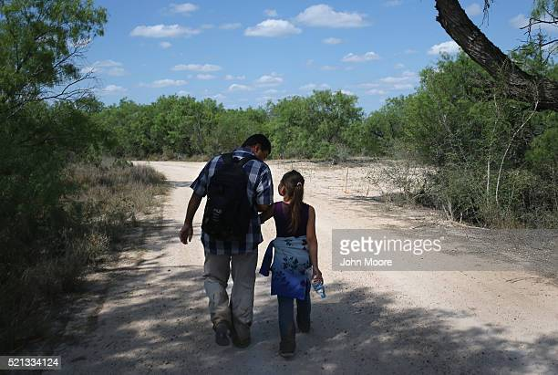 Ania from El Salvador walks with her father through the South Texas countryside after crossing the Rio Grande from Mexico into the United States to...