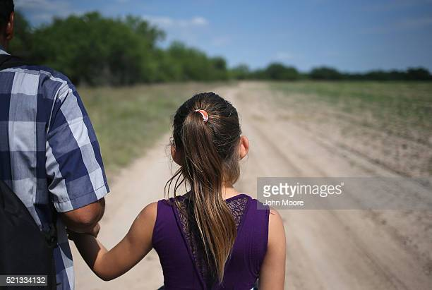 Ania from El Salvador walks with her father through the Texas countryside after crossing the Rio Grande from Mexico into the United States to seek...