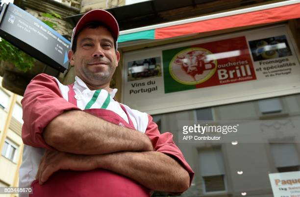 Anibal Pinto Ferreira a Portuguese butcher poses for photographs in front of a Portuguese butcher's shop EschsurAlzette on May 18 2017 The...