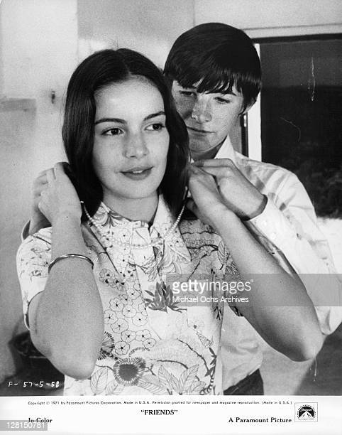 Anicee Alvina helps Sean Bury put a necklace on her in a scene from the film 'Friends' 1971