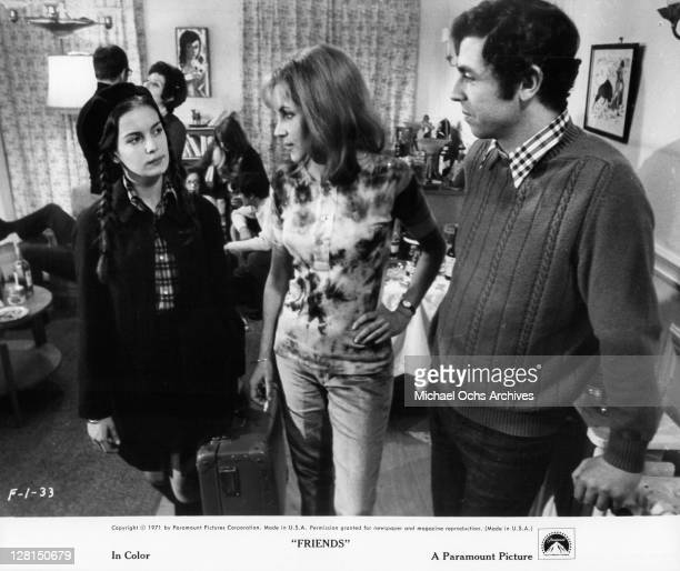 Anicee Alvina holding a suitcase looking at two unknown actors in a scene from the film 'Friends' 1971