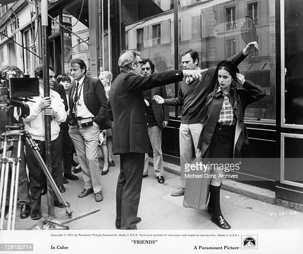 Anicee Alvina holding a suitcase with camera men surrounding her in a scene from the film 'Friends' 1971