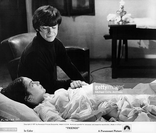 Anicee Alvina is in bed as Sean Bury sits by her side in a scene from the film 'Friends' 1971