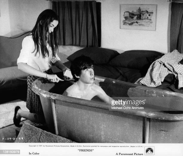 Anicee Alvina washes Sean Bury's back while he sits in the bathtub in a scene from the film 'Friends' 1971