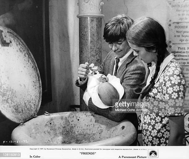 Anicee Alvina watches as Sean Bury holds a baby in a scene from the film 'Friends' 1971