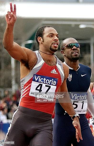 Anier Garcia of Cuba flashes the victory sign after winning the men's 110m hurdles while Allen Johnson of US smiles after coming in second place at...