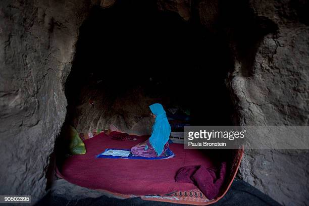 Anifa prays inside her cave dwelling where she lives with her family September 7 2009 in Bamiyan Afghanistan Many of the impoverished families living...