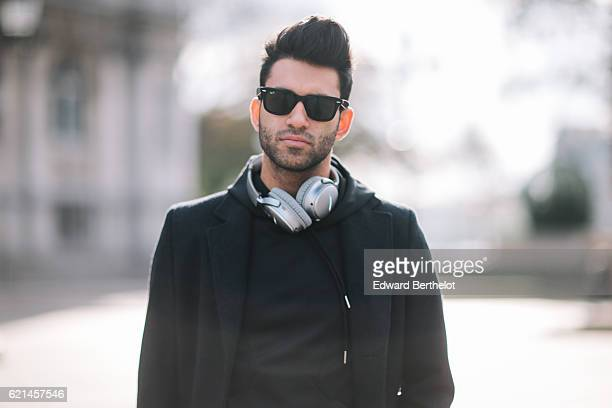 Anil Brancaleoni , is wearing Bose QC35 silver headphones, a Sandro black long coat, a Maniere de Voir pull over, Maniere de Voir black ripped pants,...