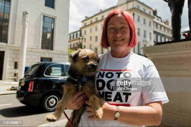 Animal Activist dressed in a white Tshirt saying Not to dog meat while holding a dog outside the Chinese embassy during a protest Animal activists...