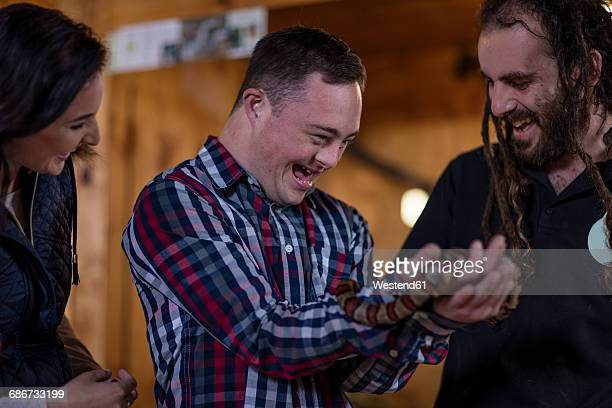 animal attendant handing over coral snake to young man with down syndrome - coral snake stock pictures, royalty-free photos & images