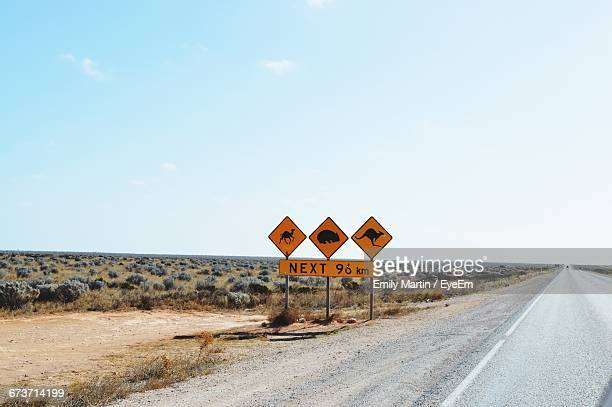 animal crossing signs by road against sky - animal crossing stock pictures, royalty-free photos & images