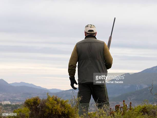 Animal hunter in the mountains with his shotgun