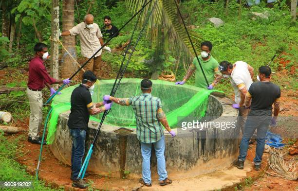 Animal Husbandry department and Forest officials inspect a well to to catch bats at Changaroth in Kozhikode in the Indian state of Kerala on May 21...