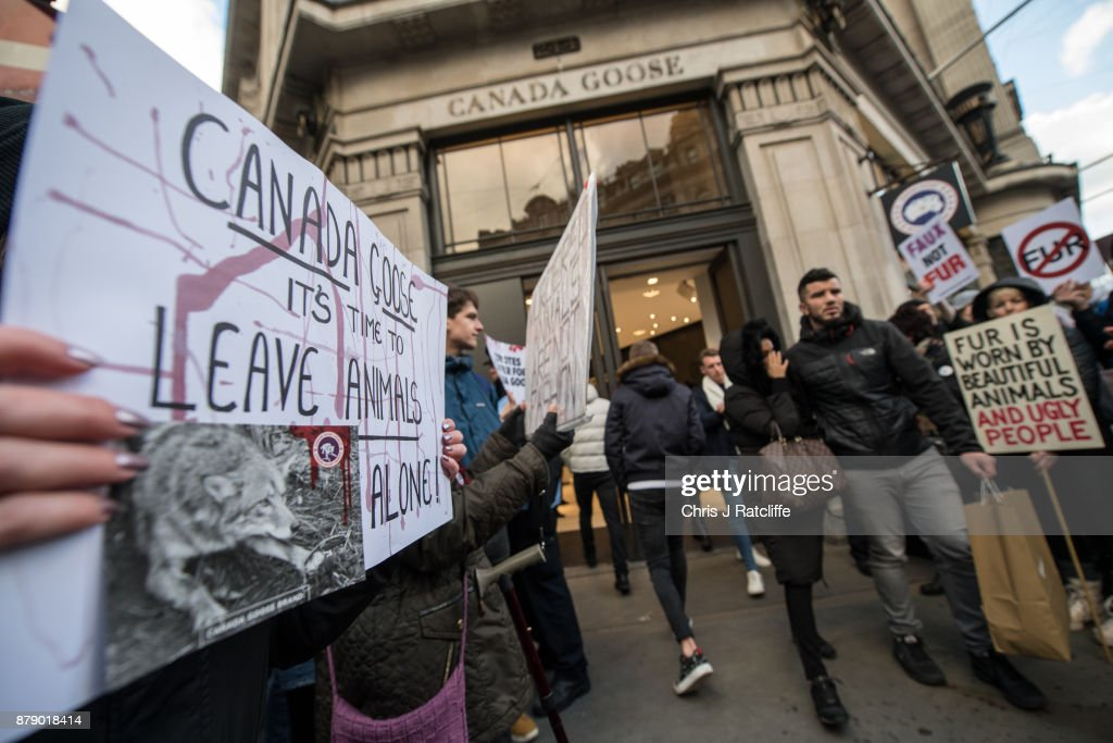 Animal rights protesters hold placards and chant as shoppers enter and leave the Canada Goose store