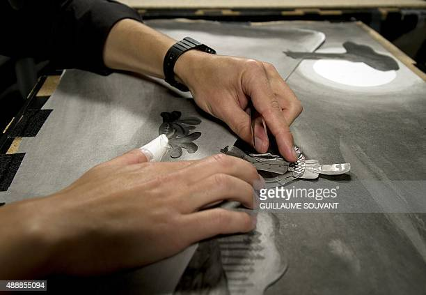 Animation artist places a figure in place in a scene during the making of an animated movie using a rostrum camera on September 17 at the new French...