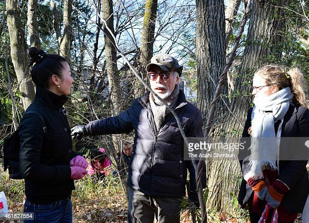 Anime director Hayao Miyazaki talks with participants in the annual cleanup of the Fuchi no Mori forest on January 18 2015 in Higashimurayama Tokyo...