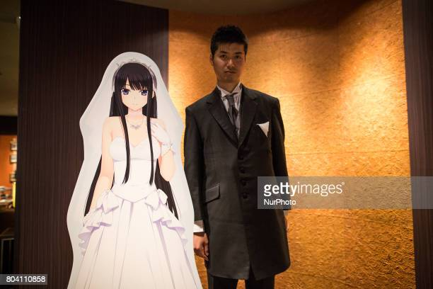 Anime fan posses with his new VR wife after a wedding ceremony in Tokyo Japan on June 30 2017 A marketing event by Japanese video game maker Hibiki...