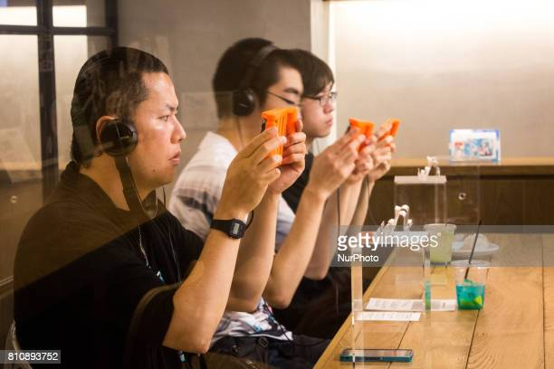 Anime fans holding a smart phone equipped with augmented reality application enjoying their virtual idol Hatsune Miku while having some sweets during...