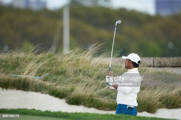 Anirban Lahiri of India and of the International Team lines up his shot from the sand trap on the 14th fairway during the third round of the...