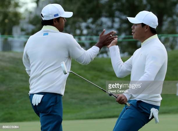 Anirban Lahiri of India and the International team is congratulated by his partner Si Woo Kim of South Korea after Lahiri had holed a crucial birdie...