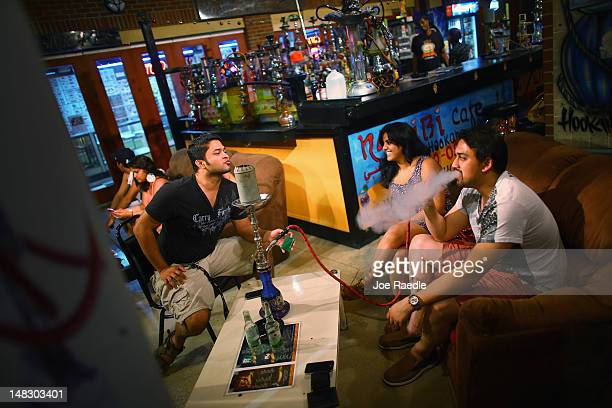 Aniruddh Nayak Yukti Ahuja and Anirudh Chaturvedi relax together at the Habibi Cafe and Hookah bar in the Ybor City neighborhood on July 12 2012 in...