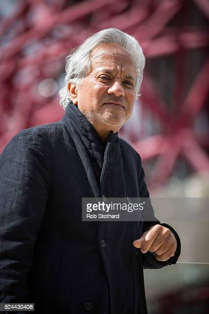 Anish Kapoor poses for photographers in front of the ArcelorMittal Orbit tower at the Queen Elizabeth Olympic Park on April 26 2016 in London England...