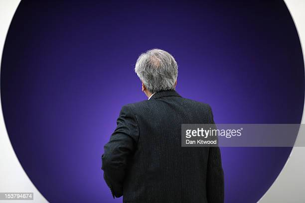 Anish Kapoor stands in front of a piece of his work entitled 'Two Blues' during a press preview at the Lisson Gallery on October 9 2012 in London...