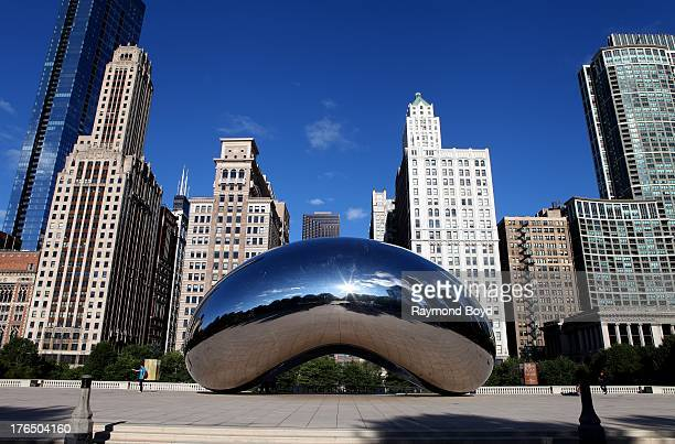 Anish Kapoor's Cloud Gate with buildings from the Michigan Avenue skyline in view in Chicago Illinois on JULY 24 2013