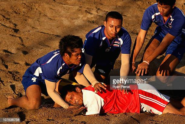 Anish Suwal of Nepal is tackled by Thailand players during the Beach Kabaddi match bewteen Nepal and Thailand at North Al Hail during day five of the...