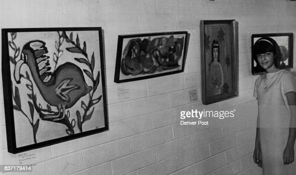 Anita Clearfield Stands Near Wall with Three of Her Oil Paintings The paintings just a few of the show are of a dodo bird an abstract and a girl...