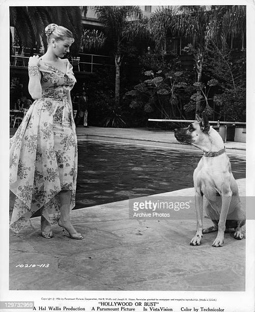 Anita Ekberg looking at big dog by the pool in a scene from the film 'Hollywood Or Bust' 1956
