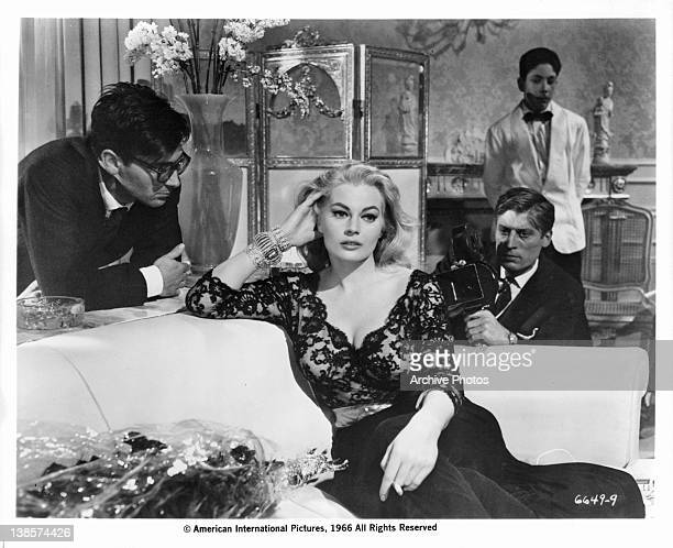 Anita Ekberg on couch brushing back her hair while unidentified men watch in a scene from the film 'La Dolce Vita' 1960