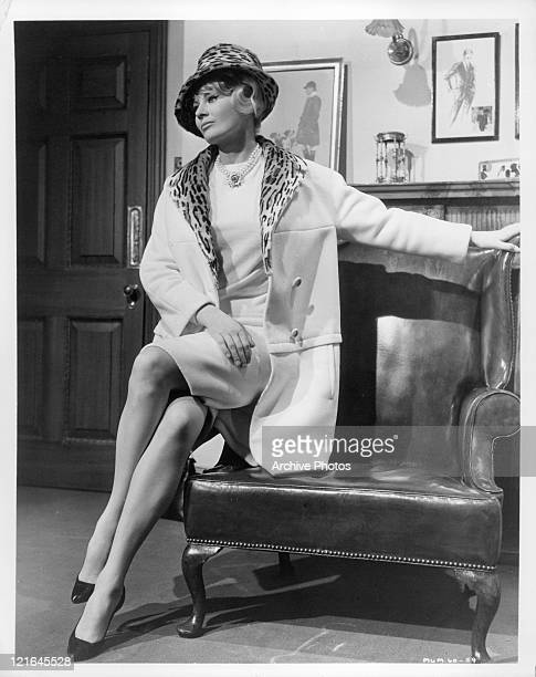 Anita Ekberg sits on arm of chair in a scene from the film 'The Alphabet Murders' 1966