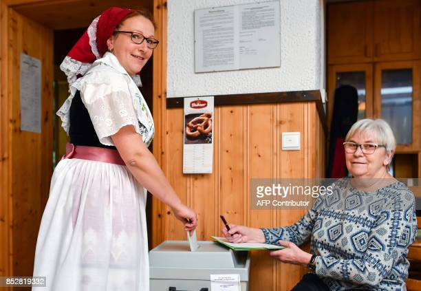 Anita Storch wears a traditional Sorbian dress as she casts her ballot at a polling station in Lehde in the Spreewald region, eastern Germany, during...