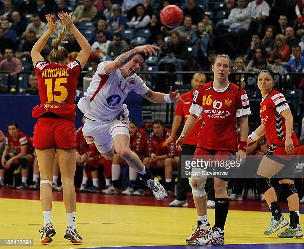 Anja Edin of Norway jump to scores past Andrea Klikovac of Montenegro during the Women's European Handball Championship 2012 gold medal match between...