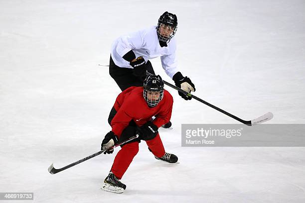 Anja Stiefel and Julia Marty of Switzerland skate during a women's ice hockey training session ahead of the Sochi 2014 Winter Olympics at the Shayba...