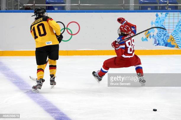 Anja Weisser of Germany checks Yekaterina Smolina of Russia during the Women's Ice Hockey Preliminary Round Group B Game on day two of the Sochi 2014...