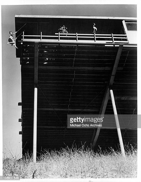 Anjanette Comer swings off a balcony in a scene from the film 'The Loved One' 1965