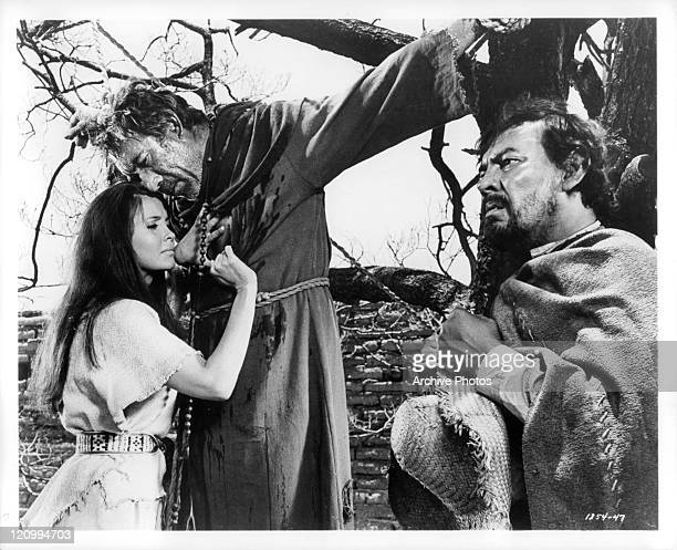 Anjanette Comer tries to comfort Anthony Quinn with Jose Chavez sitting nearby in a scene from the film 'Guns For San Sebastian' 1968