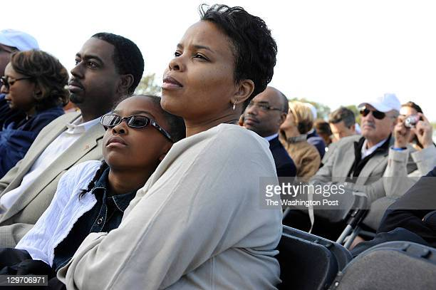 Anjanette Taylor center holds her daughter Evan Amina Taylor left center as her husband Montell Taylor left sits next to them during the Martin...