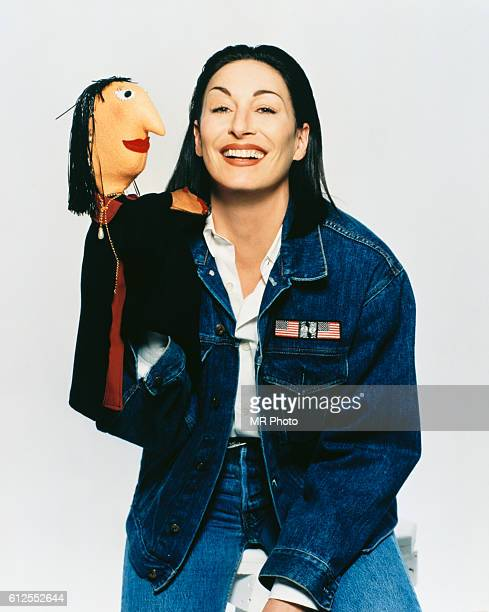 Anjelica Huston holds up a puppet made that looks like her
