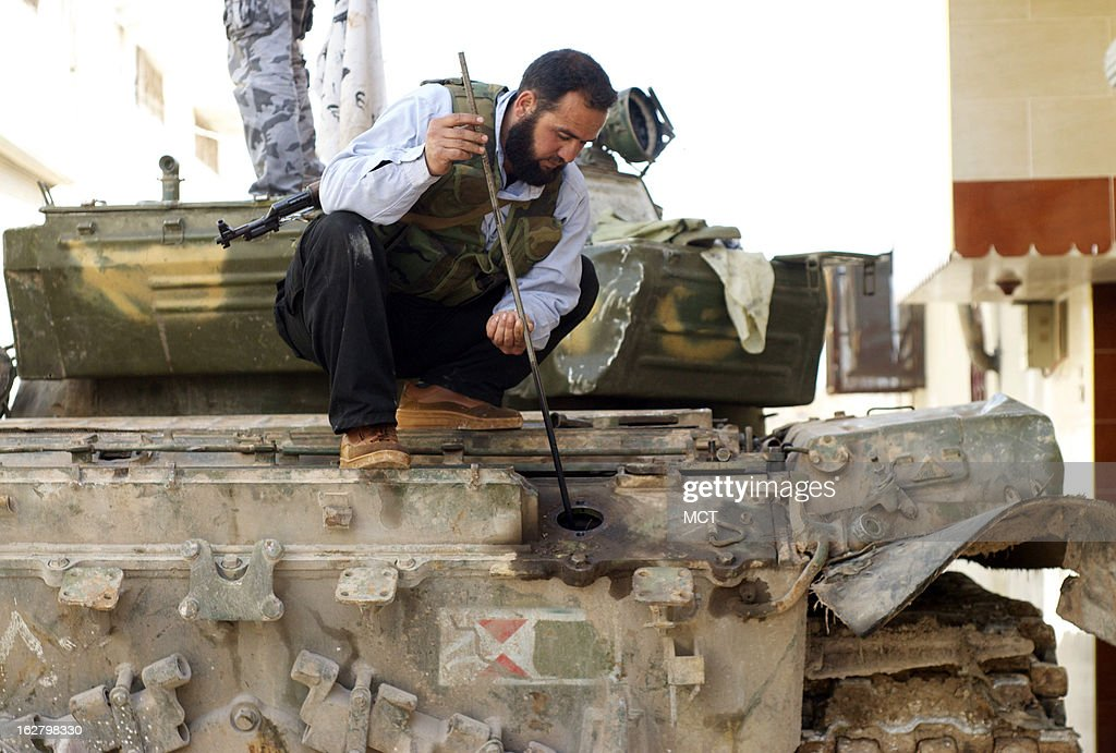 Anjir Anjir, a Syrian rebel who drives a tank, checks the oil on a captured T-72 in Kfar Nbouda, Syria, February 27, 2013. Syrian rebels are increasingly using tanks and armored personnel carriers in the fighting against the Syrian government.