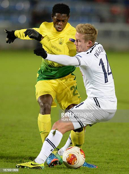 Anji's defender Ayodele Adeleye vies with Tottenham's midfielder Lewis Holtby during the UEFA Europa League Group K football match Anji Makhachkala...