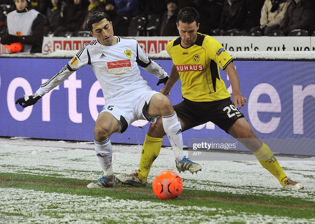 Anji's defender Odil Ahmedov (L) vies for the ball with Young Boys' forward Raphael Nuzzolo (R) during the Europa League group A football match between BSC Young Boys and FC Anji Makhachkala on Decenber 6, 2012, in Bern.