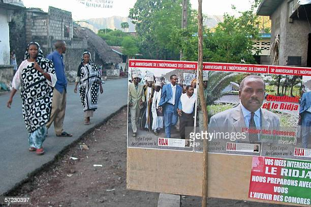 Residents of Anjouan walk past campaign posters 01 April 2006 as the Union of Comoros prepares for presidential elections on April 16 Under the terms...