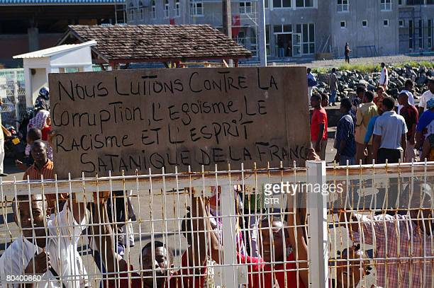 Anjouan demonstrators hold a placard reading 'We fight against corruption egoism racism and satanic spirit of France' on March 27 2008 during a...