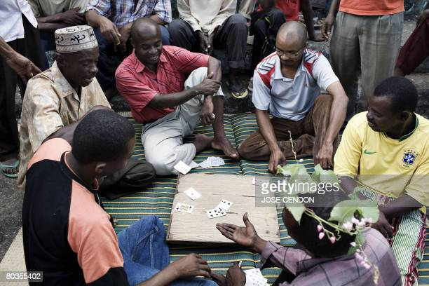 Anjouanese people play cards on a street of Mutsamudu the capital of Anjouan on March 24 2008 Two ships with troops mandated by the African Union to...