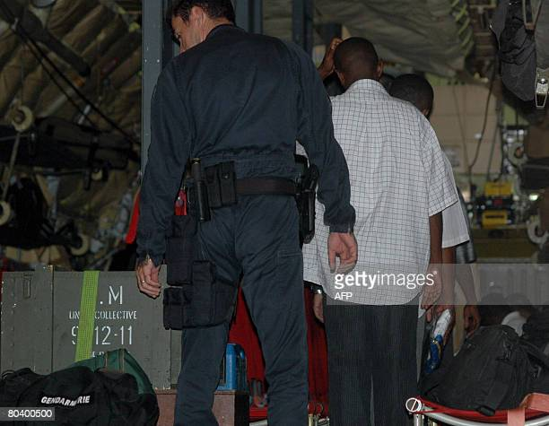 Anjouan's asylum seekers board a plane on March 27 2008 at the airport in Pamandzi Petite Terre part of the French island of Mayotte the...