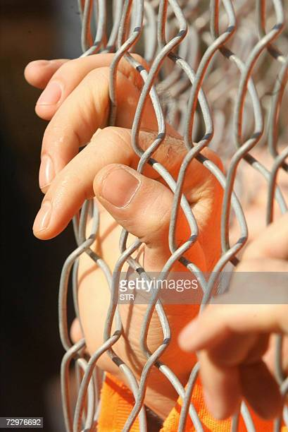 The hands of a Human rights activist are seen behind a fence dressed in orange garb as the prisoners in Guantanamo the activists are staging a silent...