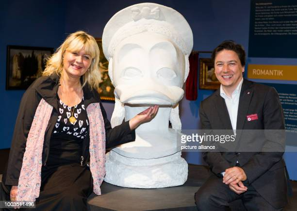 Anke Doepner director of the artist group InterDuck and RainerMaria Weiss curator of the Archäologische Museum Hamburg stand in fron of the bust of...